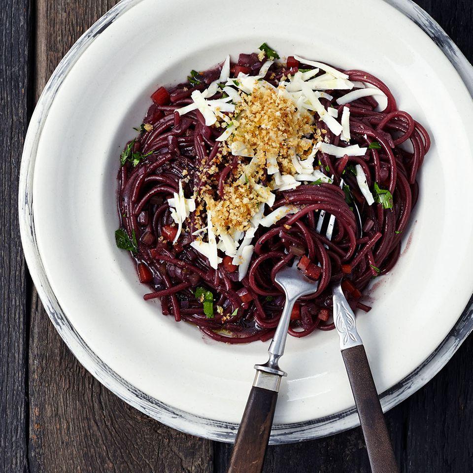 Die in Gemüse-Rotwein-Fond gegarten Spaghetti glänzen mit großem Geschmack und toller Optik.