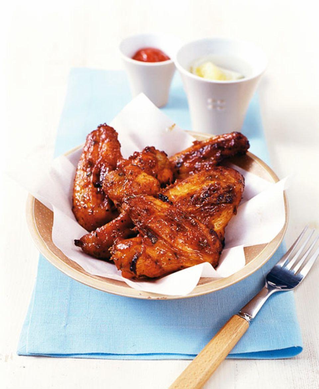 Würzige Marinade umgibt die Chicken Wings: Mit Chilisauce, Honig, Paprikapulver und Zitronensaft wird's richtig lecker