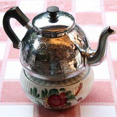 Anschließend zieht der Teeaufguss circa 5 Minuten auf dem Ofen oder einem Stöfchen. Dann wird Wasser aufgegossen. Zum Servieren kann man jede einzelne Tasse sieben, den Tee durch ein Sieb in eine (vorgewärmte) Servierkanne umgiessen oder einen Siebeinsatz für die Kanne benutzen. Viele Ostfriesen trinken ihren Tee aber auch mit den Teeblättern.