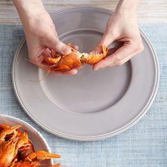 Krebse aus dem Kochtopf nehmen und kurz abkühlen lassen. Schwanzteil vom Kopf trennen, indem man Schwanz und Kopf in entgegengesetzte Richtung dreht.