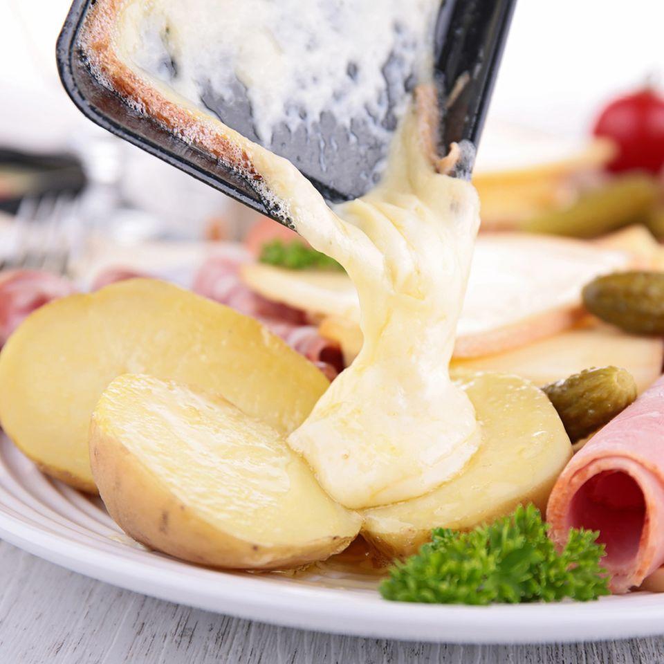 Geschmolzener Raclette-Käse aus dem Pfännchen mit Kartoffeln