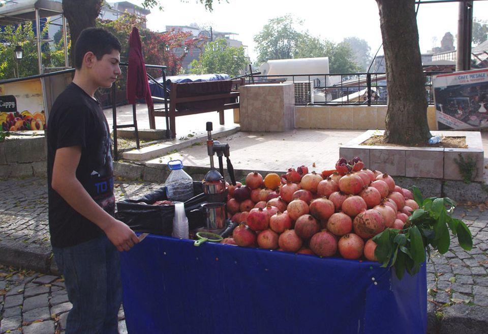 An mobilen Ständen werden Granatäpfel frisch gepresst
