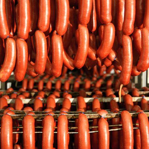 Die Würste hängen in langen Rindswurstschlangen auf dem Wurstwagen, bevor sie geräuchert und gegart werden