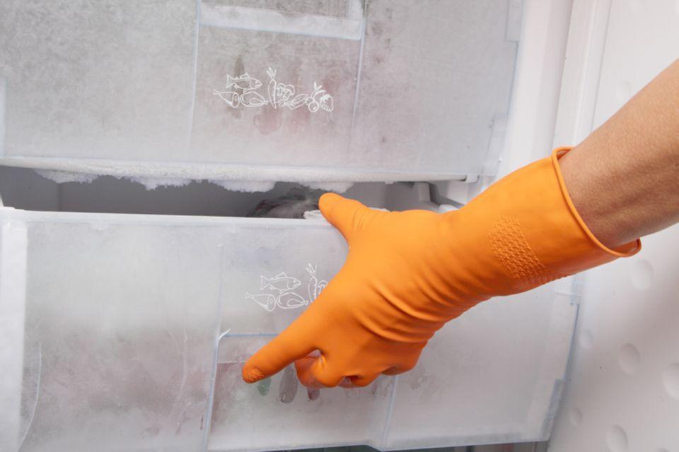 Hand in Gummihandschuh öffnet Tiefkühlschrankfach