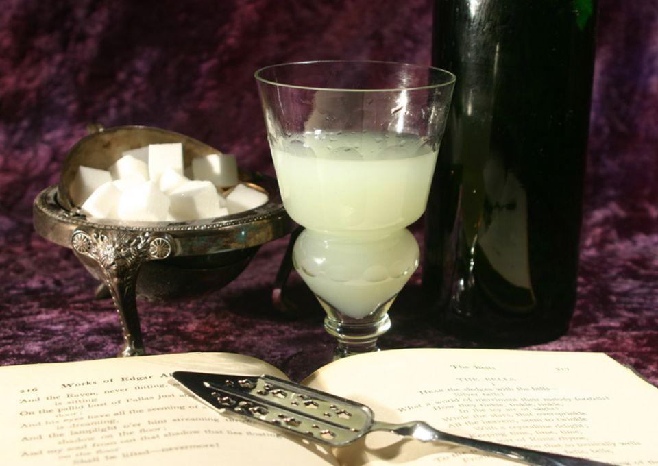 In das Glas wird bis zur Einbuchtung Absinth eingefüllt. Durch Zugabe von Wasser entsteht die Eintrübung.
