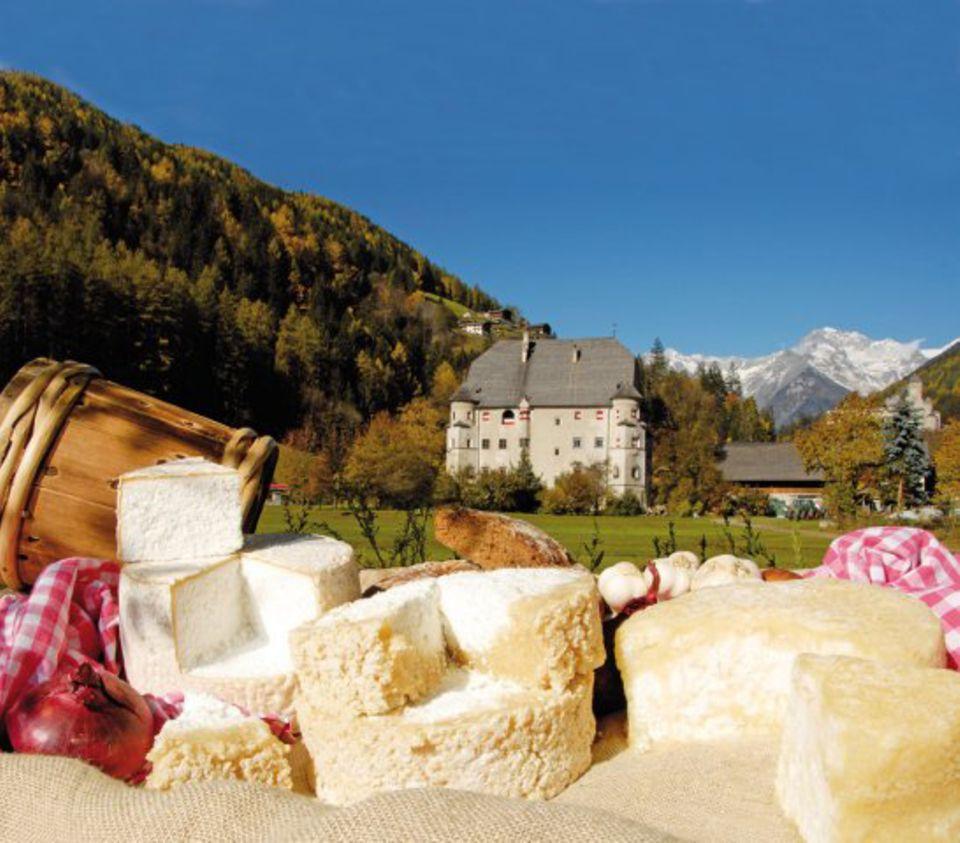 """Käse vor einem der Wahrzeichen von Sand in Taufers: Ansitz """"Neumelans"""""""