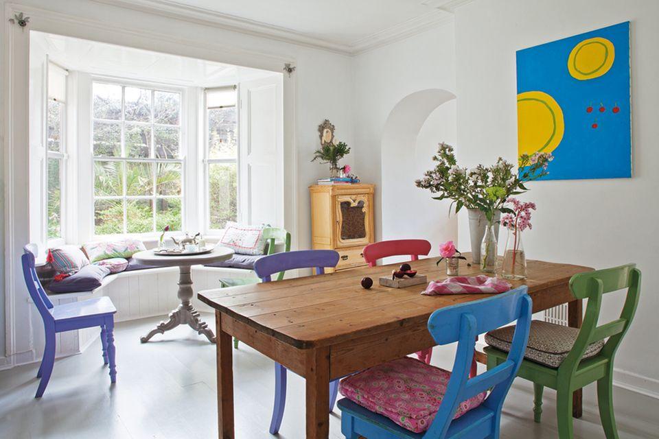 Das helle Esszimmer in der Regency-Villa in einem Vorort von Dublin - mit Kieferntisch und bunt lackierten Küchenstühlen