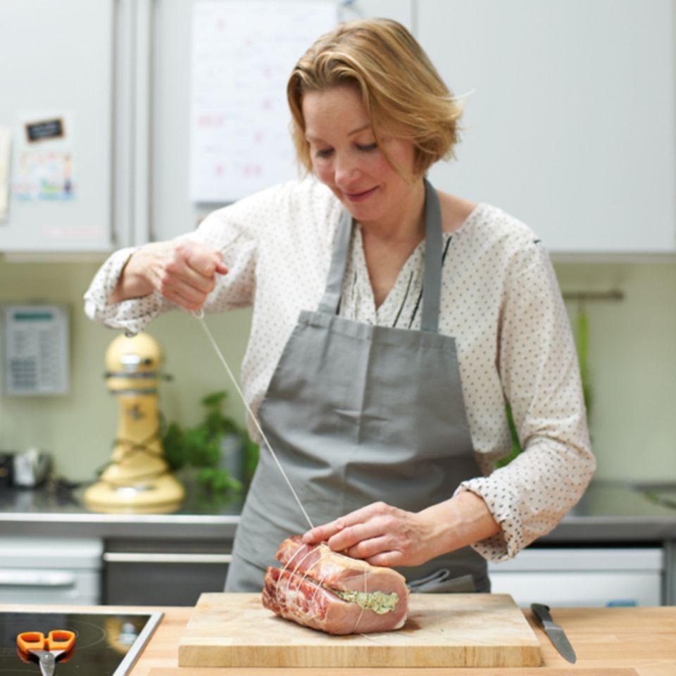 Anne Haupt umwickelt den gefüllten Kasseler Rücken mit Küchengarn