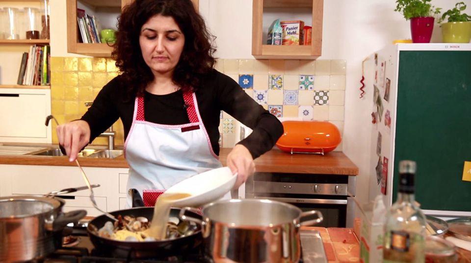 Luisa Giannitti gießt den Muschelsud in die Pfanne.