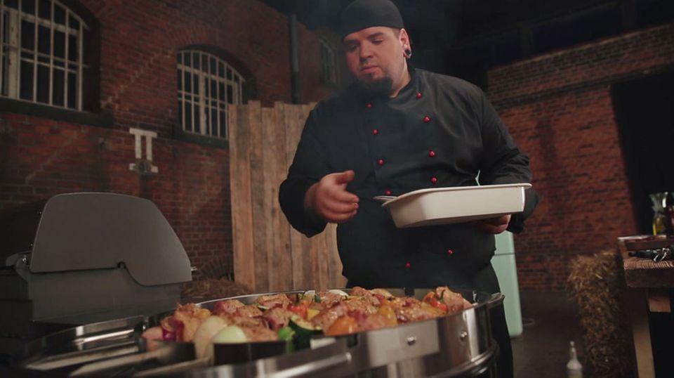 Marc Balduan bestreicht die Schaschlikspieße auf dem Grill mit Marinade.