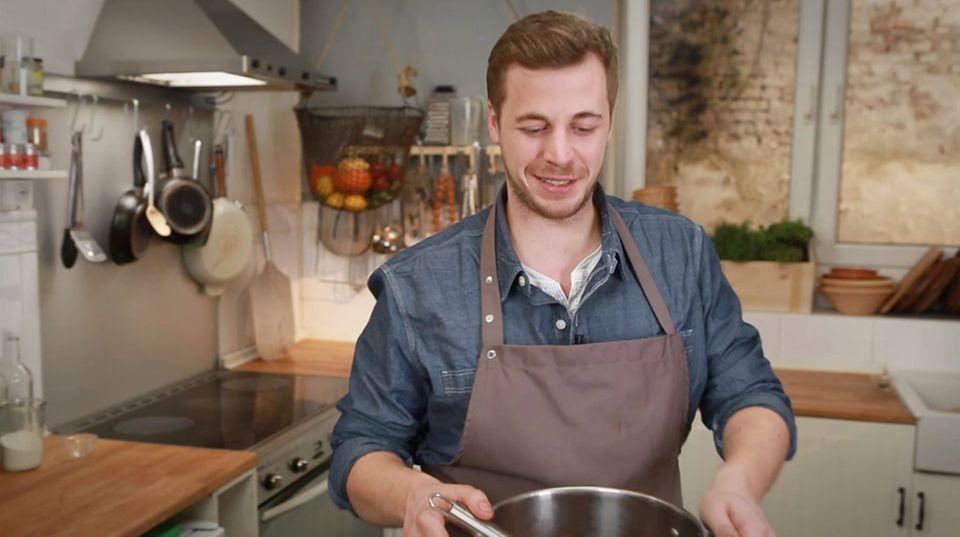 Fabio Haebel kocht die Braune Jus in einem großen Topf.