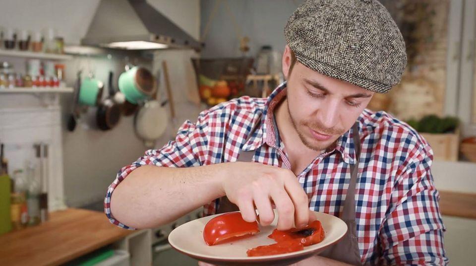 Fabio Haebel zieht die Schale der Paprika ab.