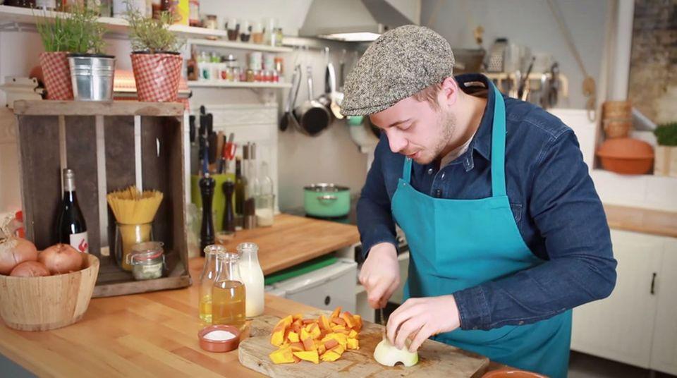 Fabio Haebel bereitet die Kürbissuppe mit Zwiebeln zu.