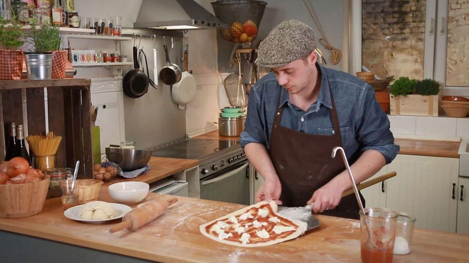 Fabio Haebel bringt seine Pizza in den Backofen.