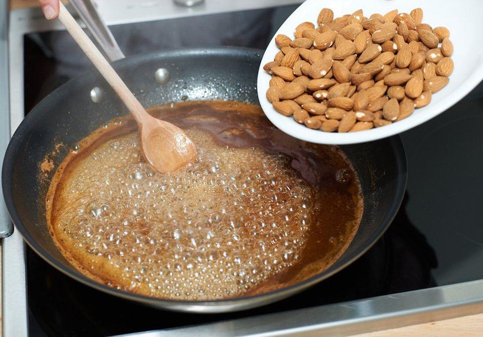 Mandeln zu Zucker-Wasser in Pfanne geben