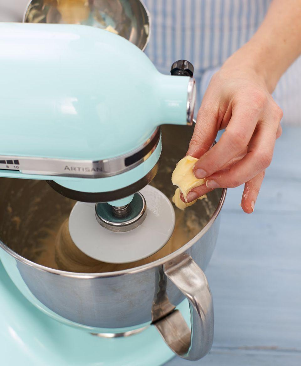 Für den Teig Butter in Stückchen in die laufende Küchenmschine geben