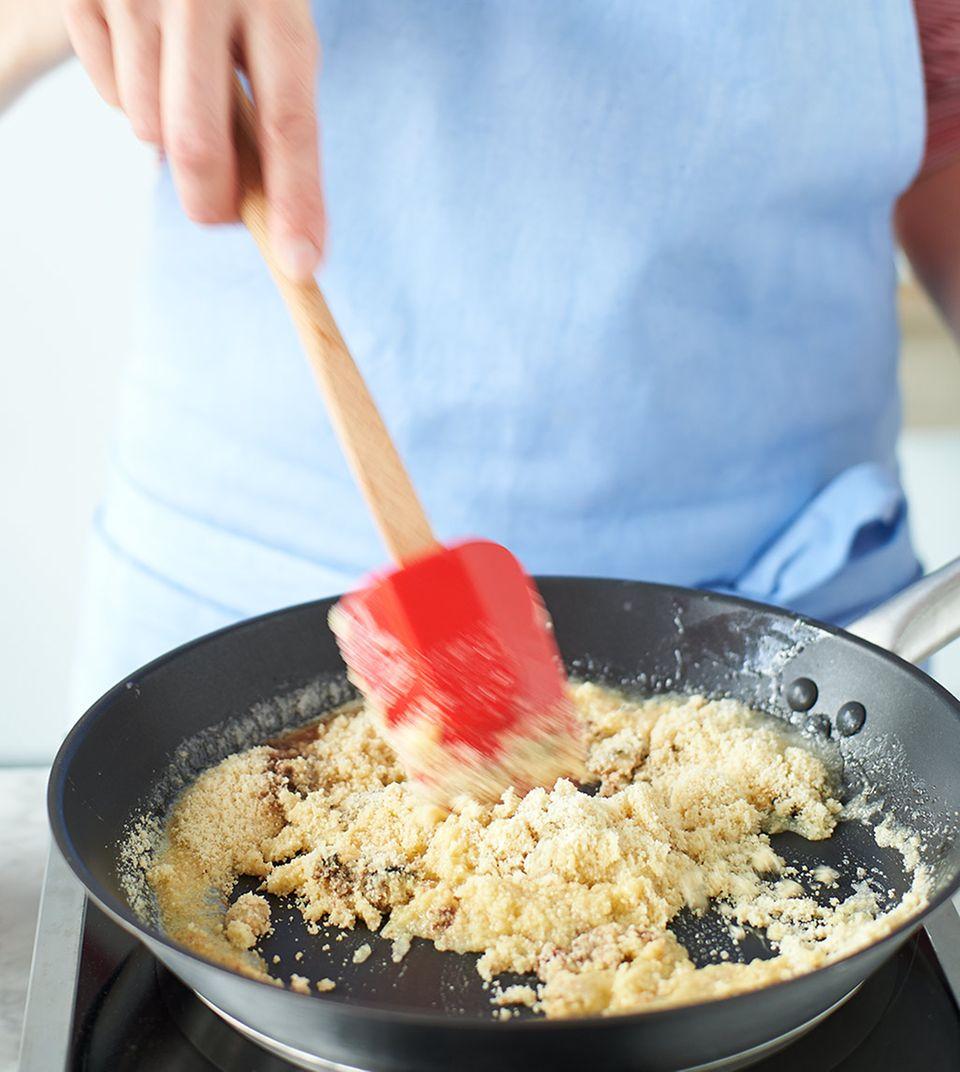 Zucker-Mandel-Butter-Mischung in einer Pfanne fein rösten