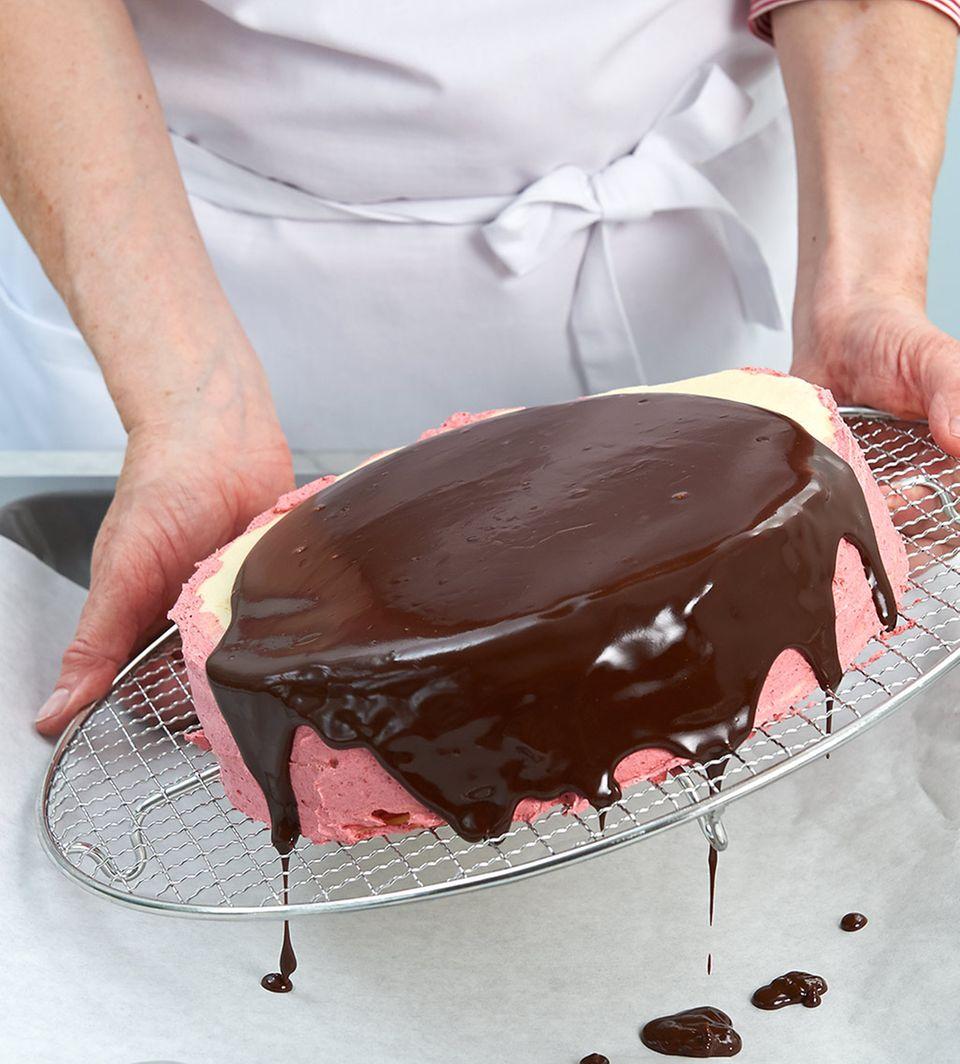 Schokoladenglasur auf Prinzessinnentorte verteilen