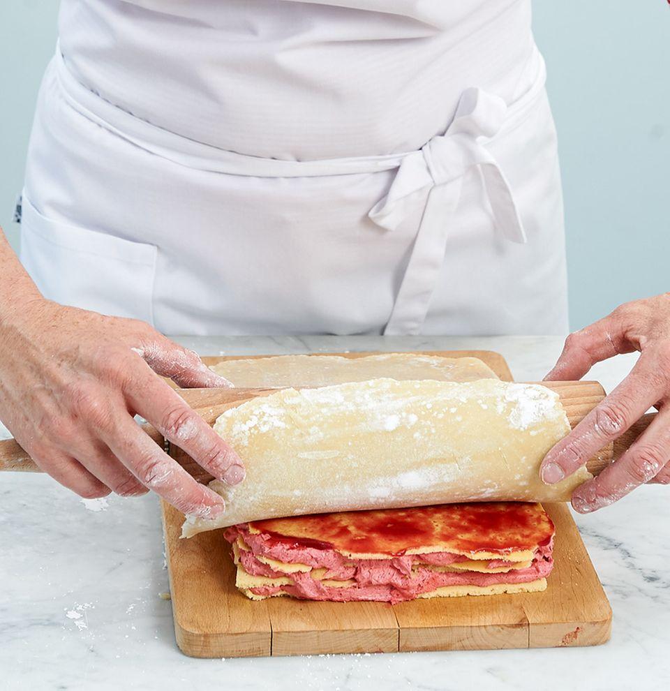 Marzipan mithilfe von Rollholz auf Kuchen abrollen