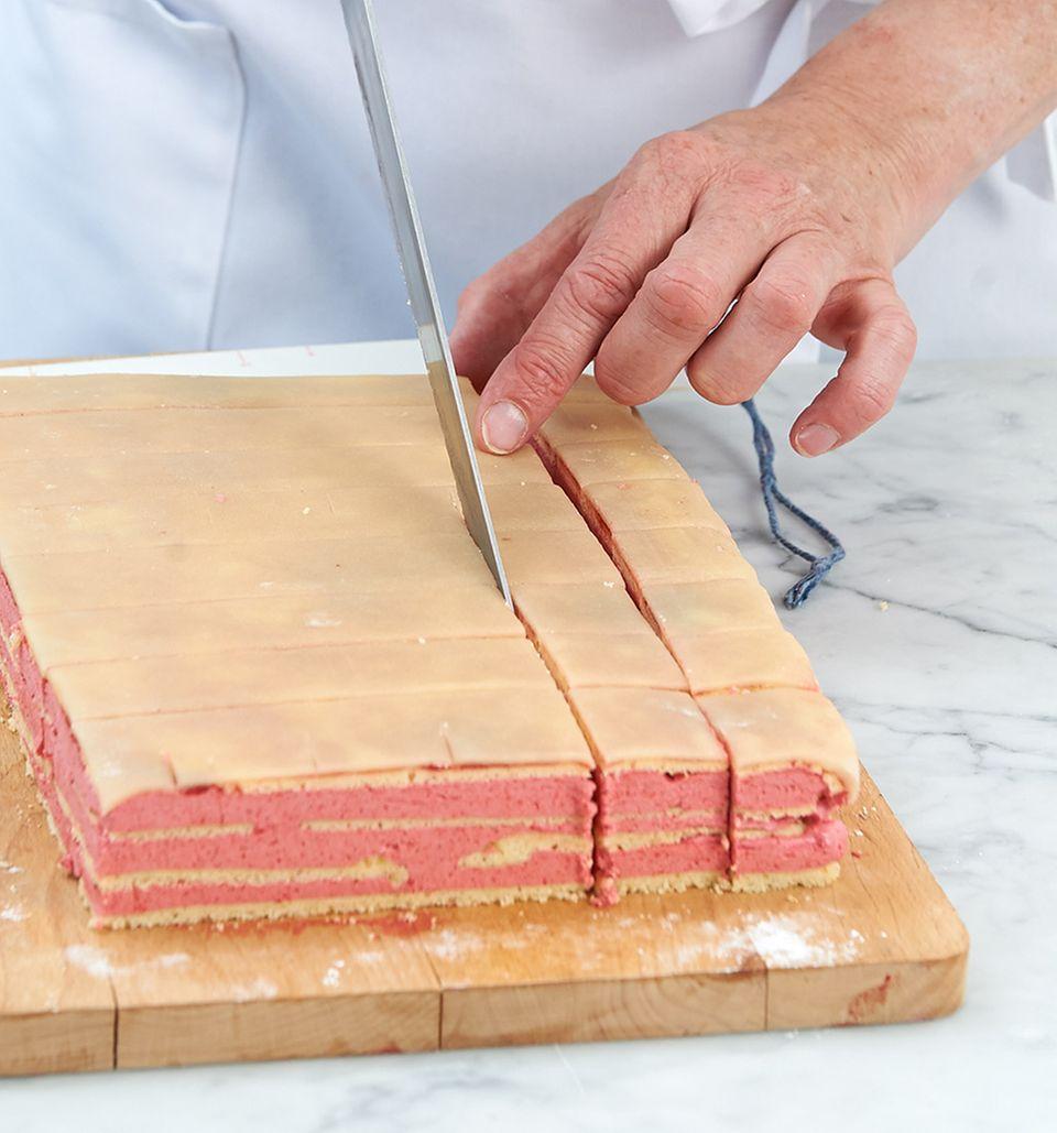 Kuchen mit einem scharfen Messer in Würfel schneiden