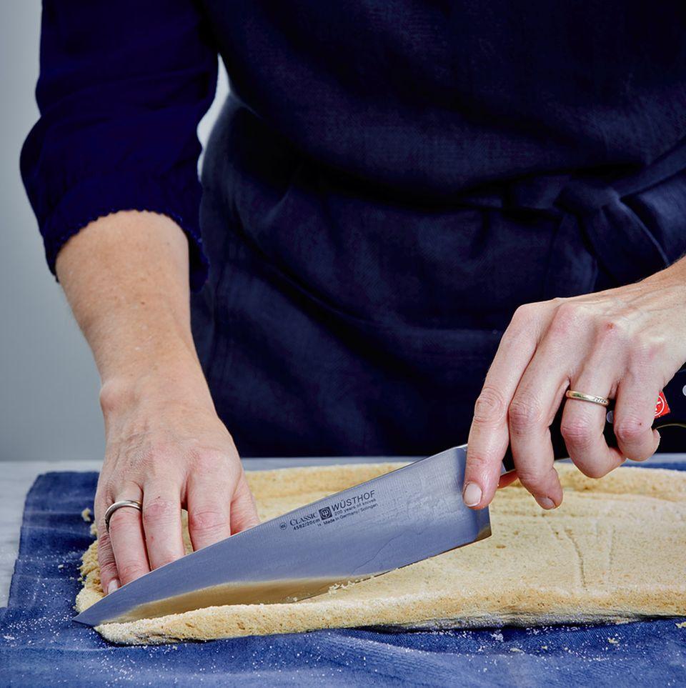 Biskuit auf dem Küchentuch mit einem Messer zuschneiden