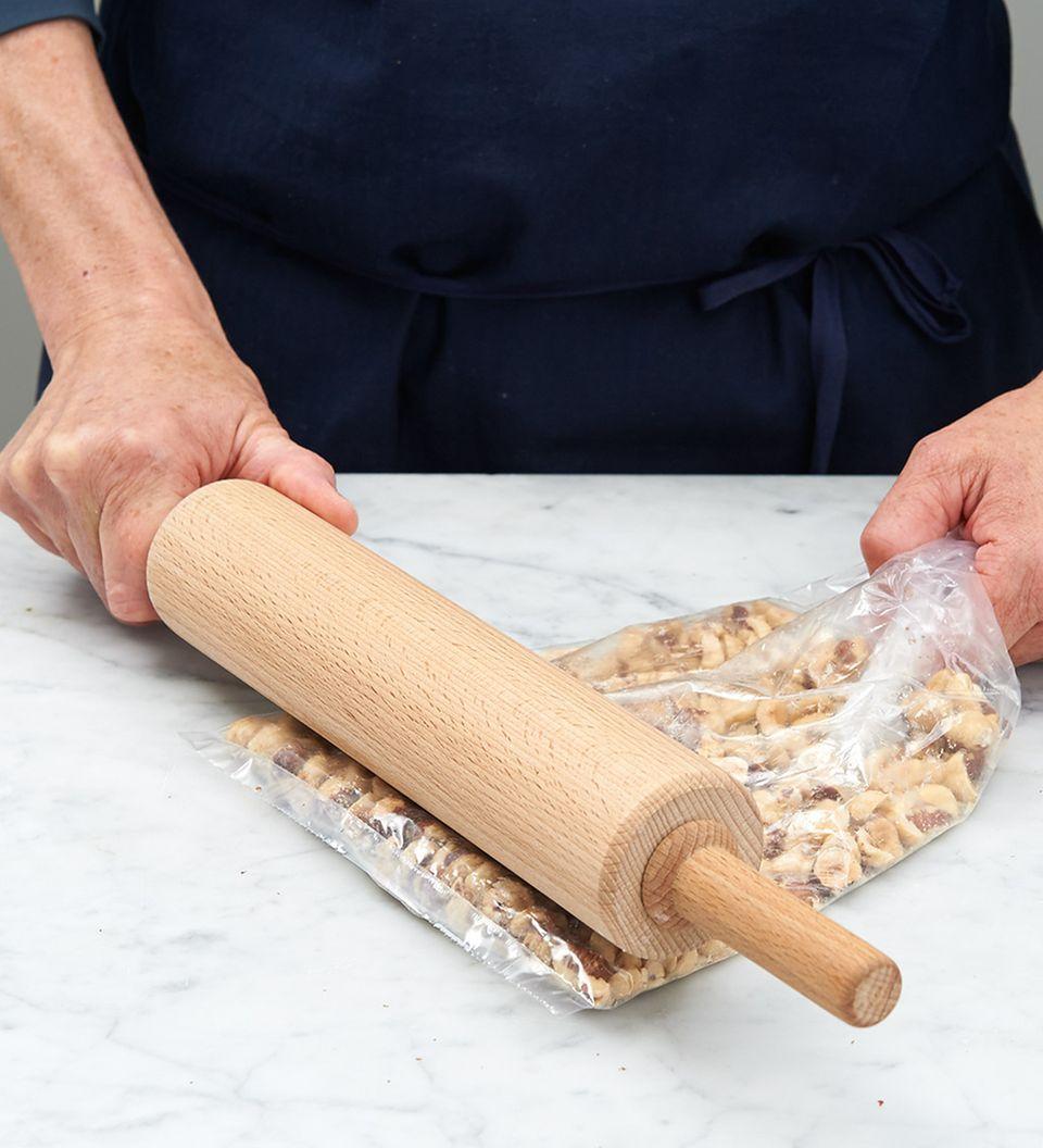 Haselnüsse in einem Gefrierbeutel mit einem Rollholz zerkleinern