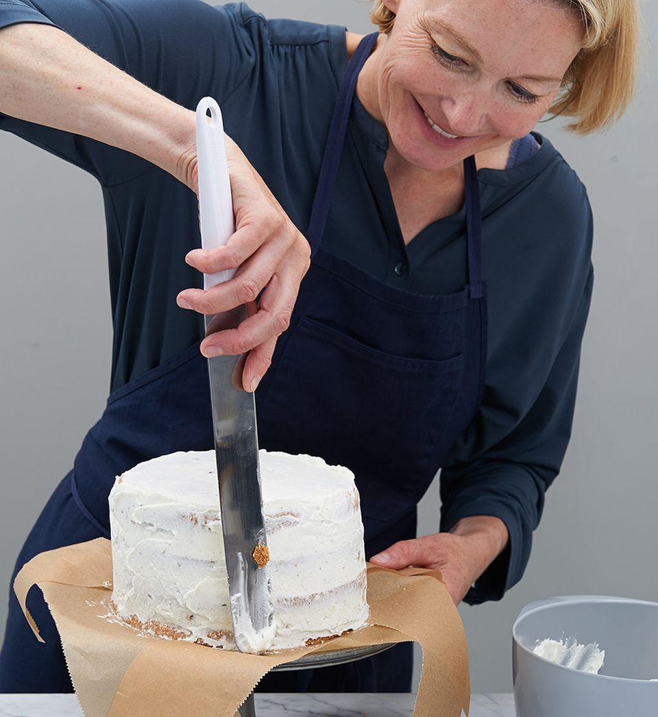 Sahne mit Palette um Torte streichen