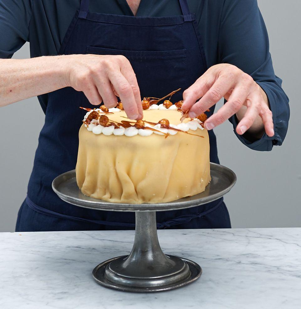 Die Torte mit feinen Karamellnüssen verzieren