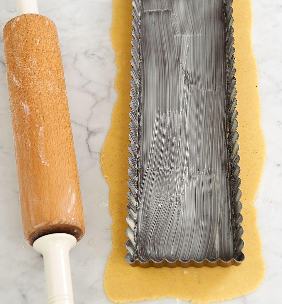 Die Tarteform ist hilfreich, um den Teig auf die richtige Größe auszurollen
