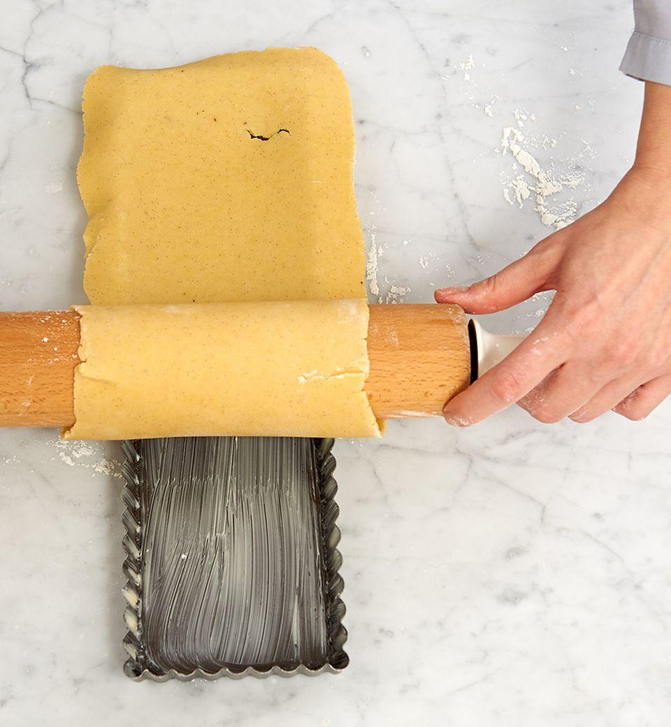 Um das Rollholz gewickelt lässt sich der Teig ganz einfach in die Tarteform legen