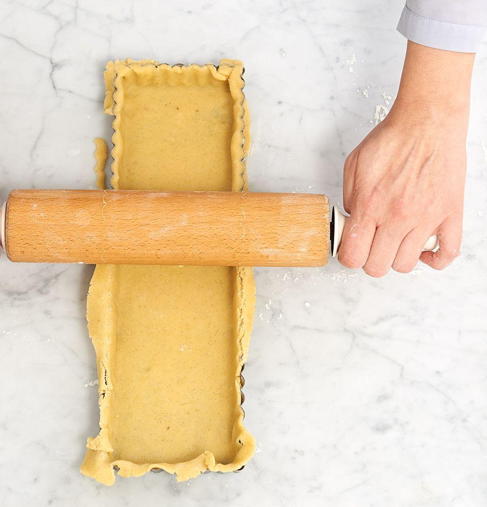 Teig in der Tarteform mit dem Rollholz begradigen