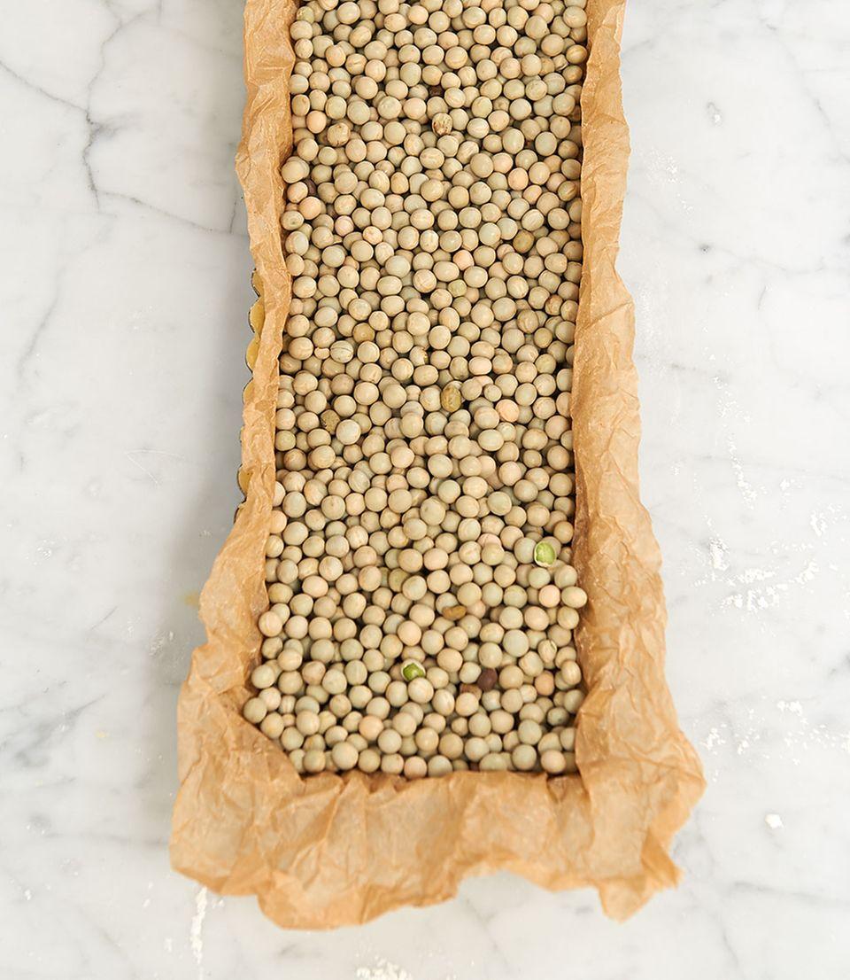 Teig und Backpapier in der Tarteform mit Hülsenfrüchten gefüllt