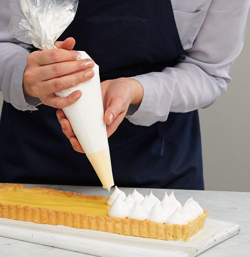 Baisertupfen mit der Spritztülle auf die Tarte spritzen