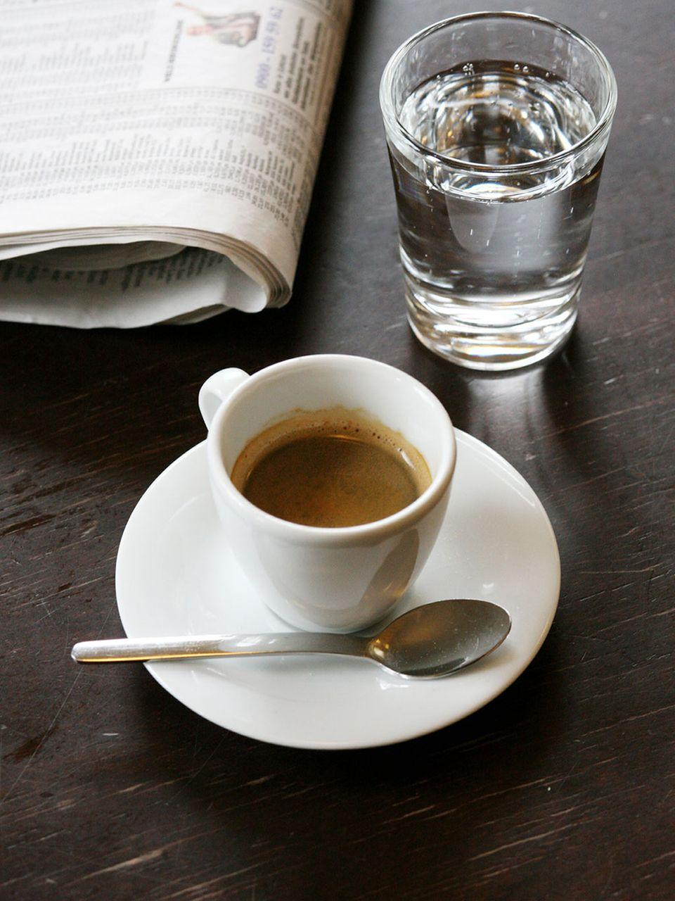 Espresso in Tasse mit einem Glas Wasser