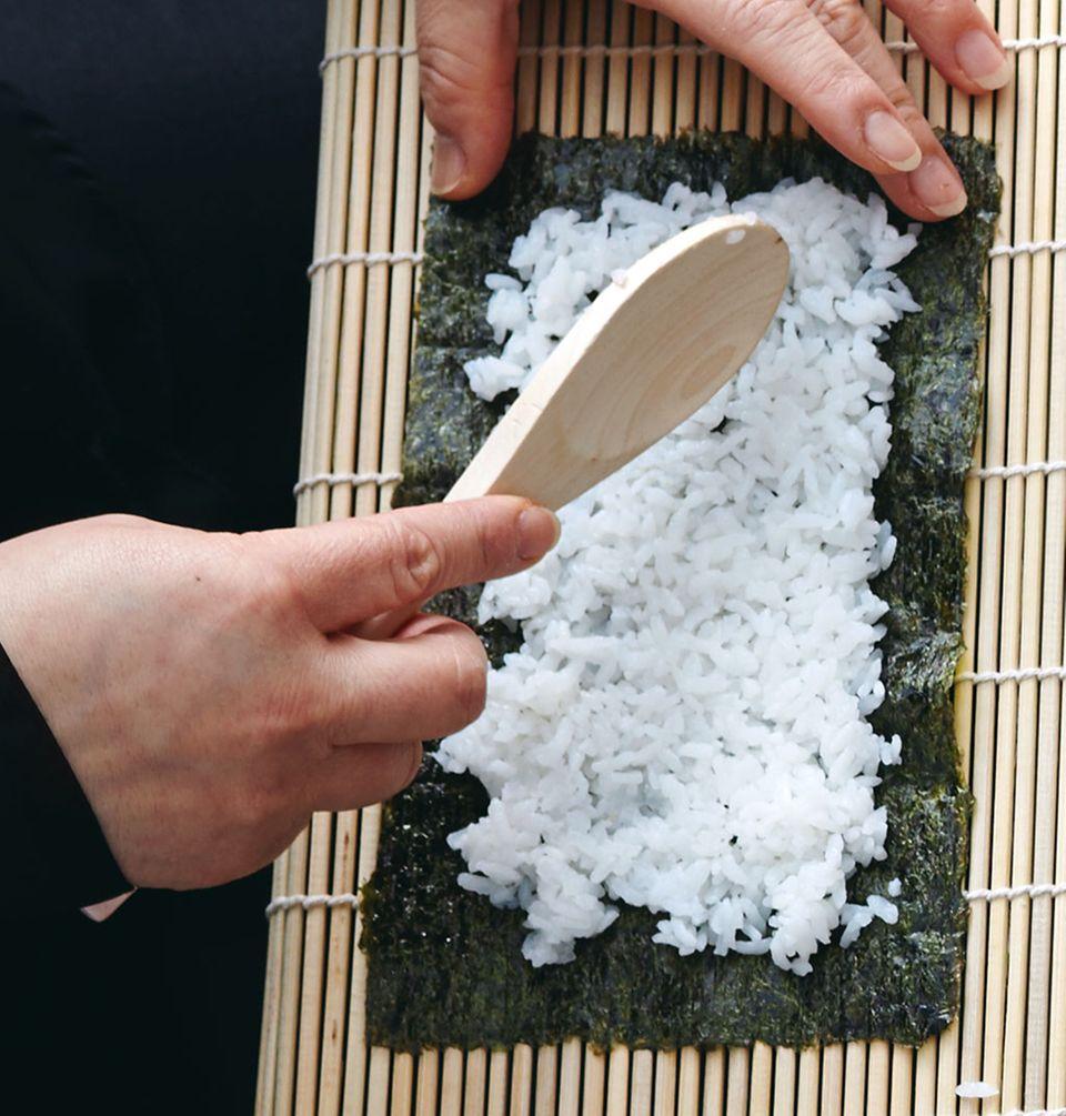 Sushirollen werden mit einer Bambusmatte in Form gebracht.