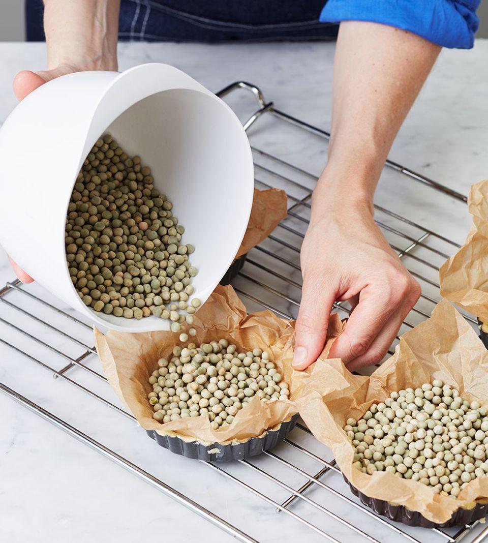 Hülsenfrüchte zum Blindbacken in die mit Backpapier belegten Tarteformen geben - so hält der Teig seine Form
