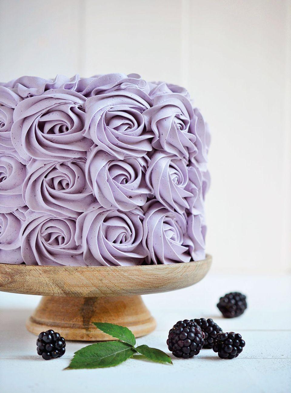 Rosen aus Brombeercreme zieren diese Torte. Im Inneren versteckt sich saftig leckerer Schoko-Biskuit!