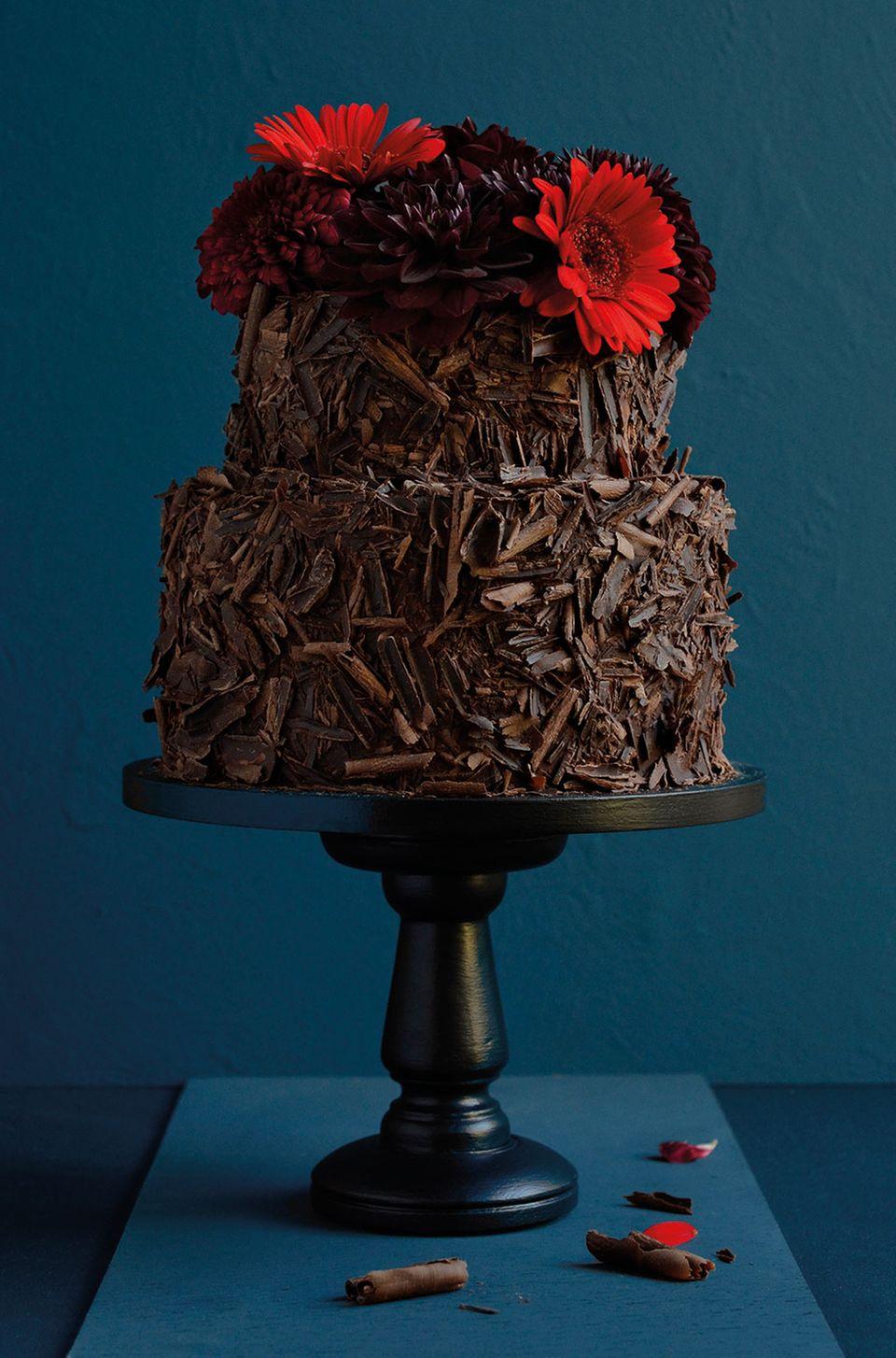 Diese Schokoladentorte mit Schokoraspeln zieren Blumen in leuchtend dunkelroten Nuancen