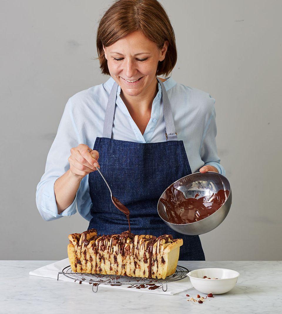 Die flüssige Schokolade in dünnen Strichen über das Zupfbrot geben