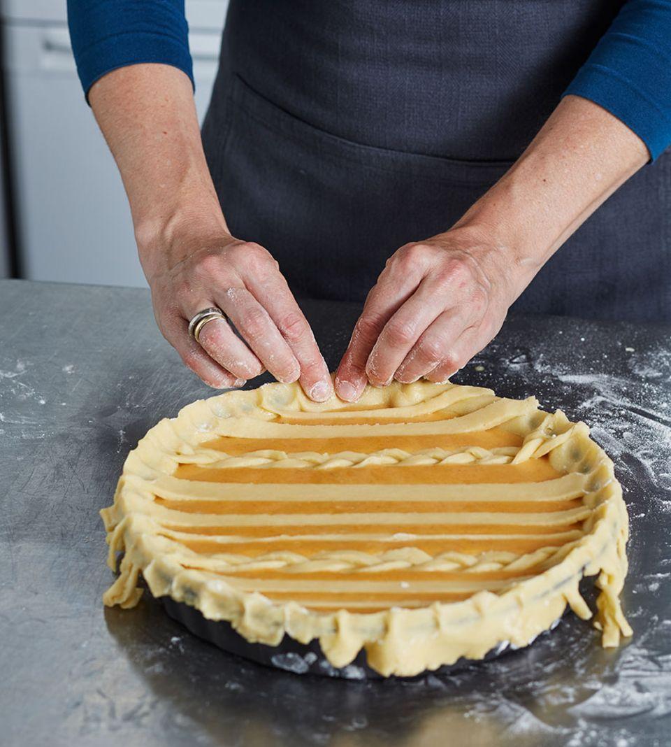 Die Enden der Teigstränge mit den Fingern fest in den Pie-Rand drücken und fixieren