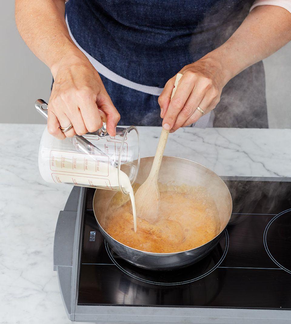 Sahne in die Zuckermasse einrühren und kurz aufkochen lassen