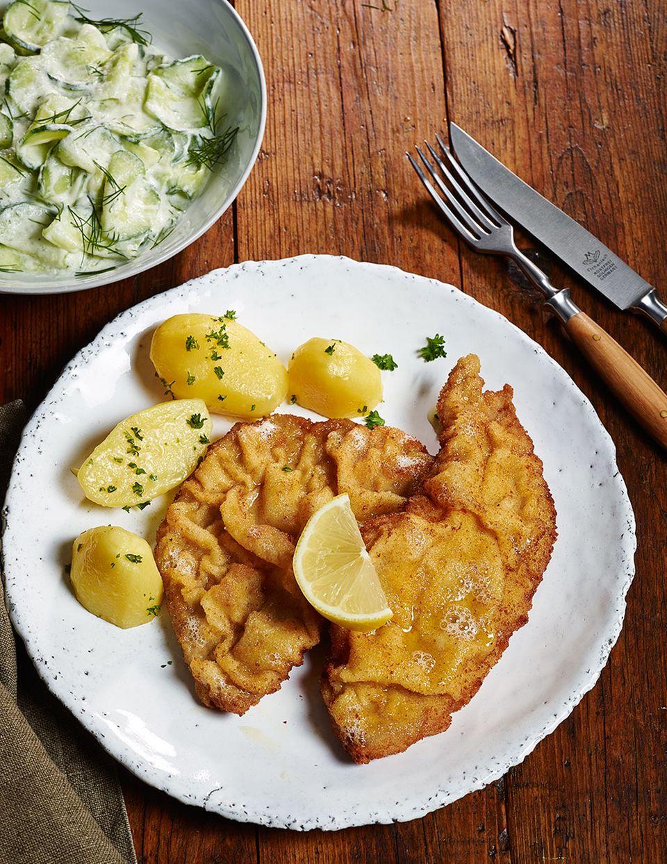 Wiener Schnitzel serviert mit Petersilienkartoffeln, Gurkensalat und Zitronenspalten