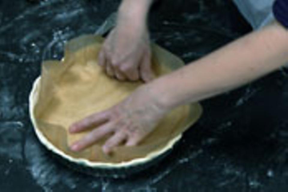Zum Blindbacken Backpapier auf den Teigboden legen