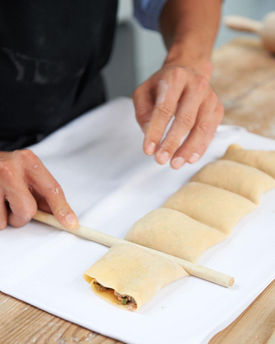 Die Maultaschenrolle mithilfe eines Kochlöffelstiels unterteilen