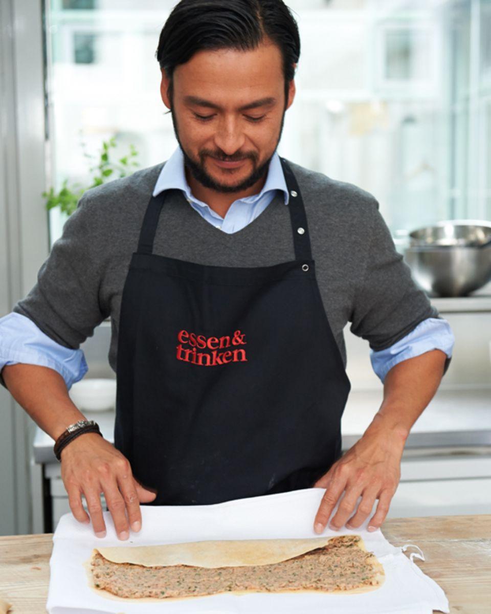 Marcel Stut rollt mithilfe eines Küchentuchs die Maultaschenrolle auf