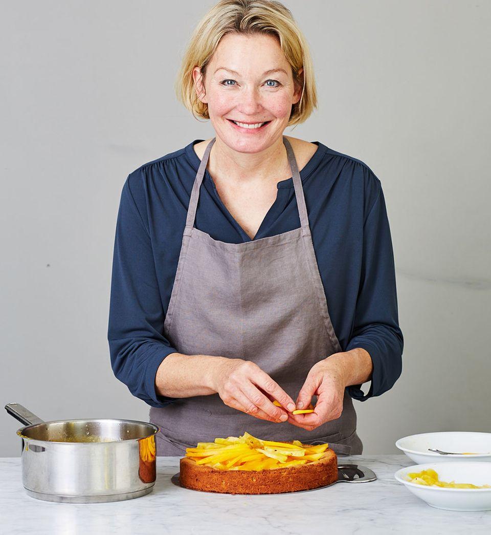 »e&t«-Backexpertin garniert den Kuchen mit dünnen Mango-Spalten.