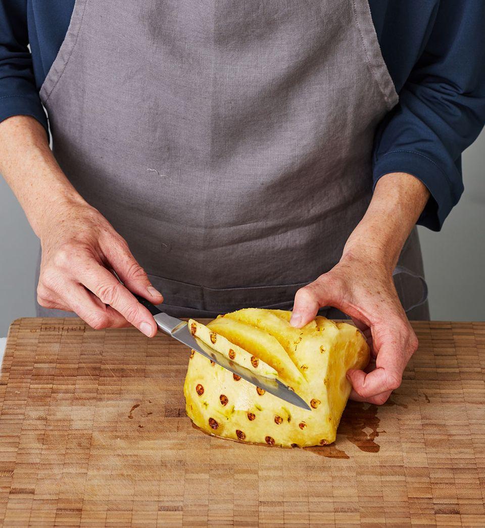 Ananas schälen und die Augen entfernen.