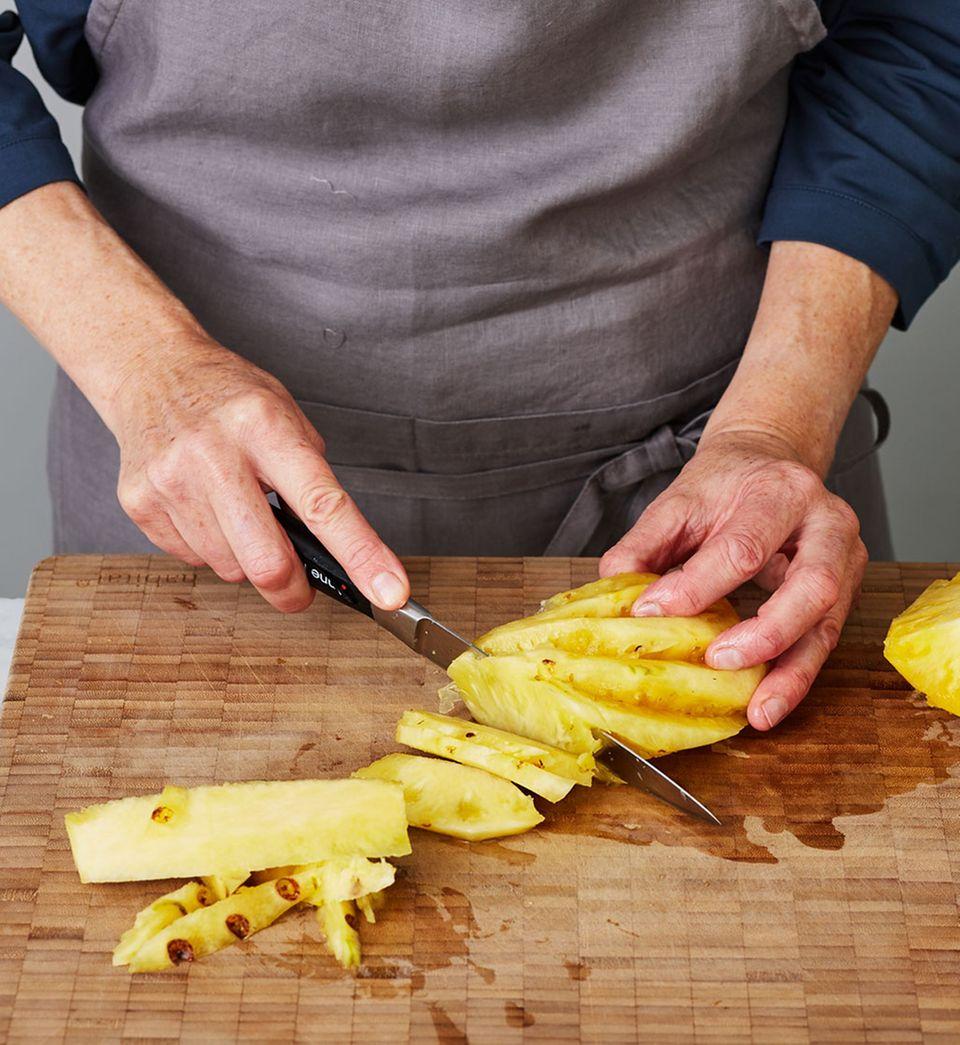Ananas-Viertel in dünne gleichmäßige Spalten schneiden, damit sie einheitlich backen.