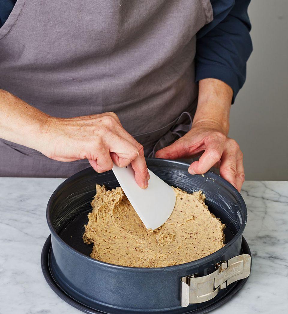 Mandelteig in die Form füllen und bis zum Rand glatt streichen.