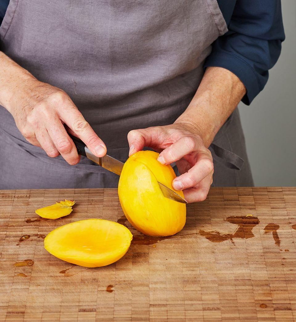 Mangofleisch vom Stein schneiden.